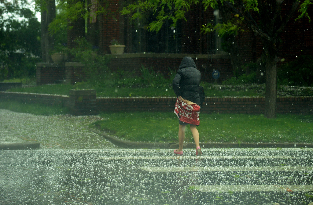 . DENVER MAY 22: A person across the street in the hail covering by herself with plastic bag at the corner of Grant St. and 10th ave. in Denver. Afternoon storm hit Downtown Denver. Denver, Colorado. May 22. 2014. (Photo by Hyoung Chang/The Denver Post)