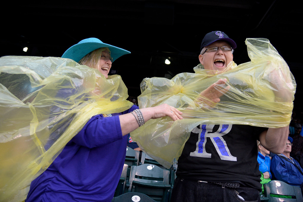 . DENVER, CO - MAY 22: Ann Benefield helps her husband Donnie Benefield with his ran poncho during the Colorado Rockies San Francisco May 22, 2014 at Coors Field. (Photo by John Leyba/The Denver Post)