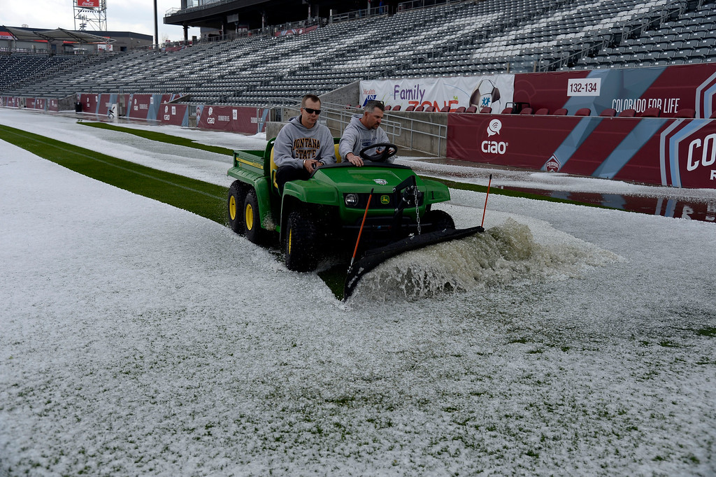 . COMMERCE CITY, CO - MAY 21: Cody Witham (L) and Phil McQuade test the turf as they plow a section of the turf at Dick\'s Sporting Goods Park. Hail pounded Commerce City blanketing the field at Dick\'s Sporting Goods Park May 21, 2014 where they will hold the class 4A and 5A state soccers finals. (Photo by John Leyba/The Denver Post)