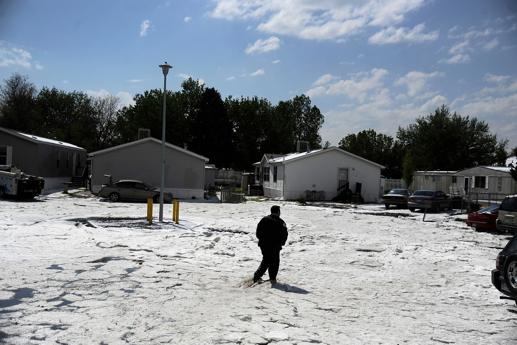 . AURORA, CO - MAY 21: Joe Furnari walks through the aftermath after hail pounded Woodshire Mobile Park. A hail storm hit the Denver metro area on Wednesday, May 21, 2014. (Photo by AAron Ontiveroz/The Denver Post)