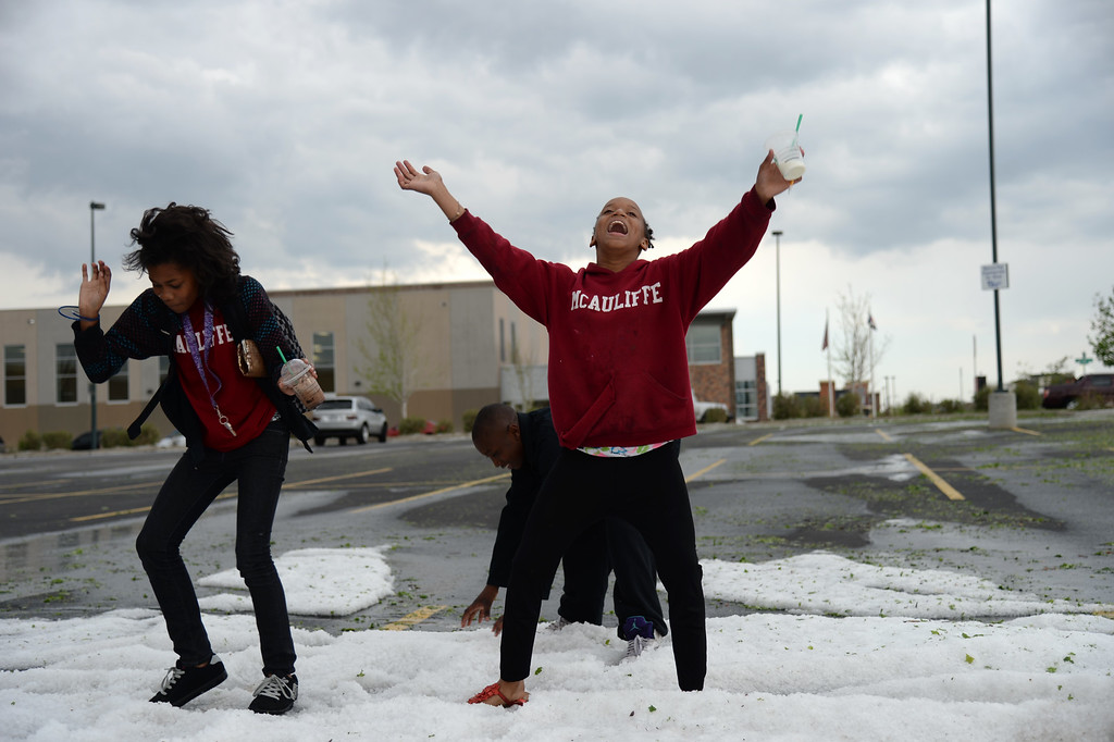 . DENVER MAY 21: Jessica Smith, 12, left, and Jenessa Williams, 12, of McAuliffe International School are dancing and playing on the hail in a parking lot at Quebec Square. Denver, Colorado, May 21, 2014. A storm pounded parts of the Denver metro area on Wednesday afternoon. (Photo by Hyoung Chang/The Denver Post)