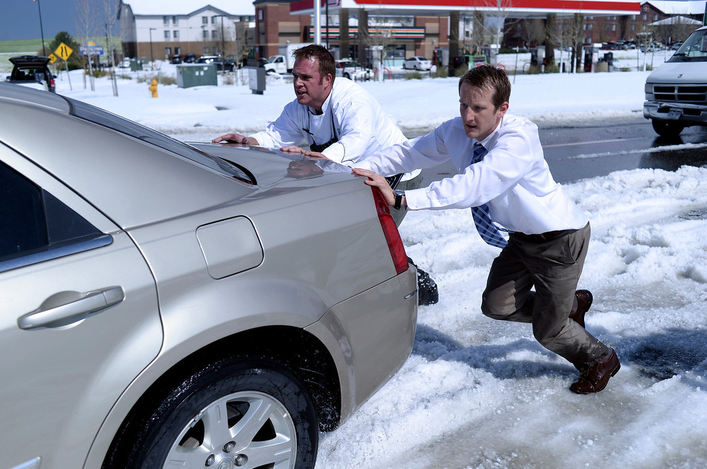 . DENVER, CO - MAY 21: Chris Collins, left, and Paul Nellis, right, pushed a motorist out of the median on Tower Road Wednesday afternoon. Hail piled more than a foot high on Tower Road stranded several vehicles following a storm that had both heavy rain and hail.  Both men work at the Embassy Suites hotel near the airport. (Photo by Karl Gehring/The Denver Post)