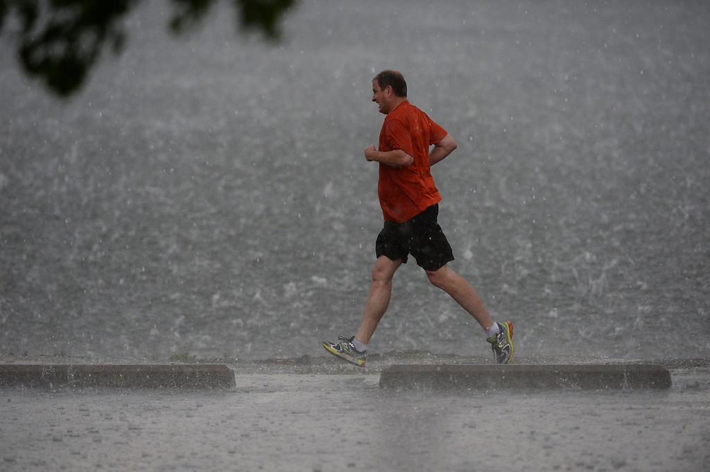 . A man sprints to his car at Washington Park as during a heavy rain/hail storm  Wednesday afternoon, May 21, 2014. (Photo By Andy Cross / The Denver Post)