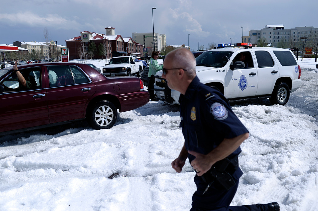 . DENVER, CO - MAY 21: A Denver Police officer used his vehicle to push a motorist out of the median of Tower Road south of the airport. Hail piled more than a foot high on Tower Road stranded several vehicles following a storm Wednesday afternoon, May 21, 2014.  (Photo by Karl Gehring/The Denver Post)