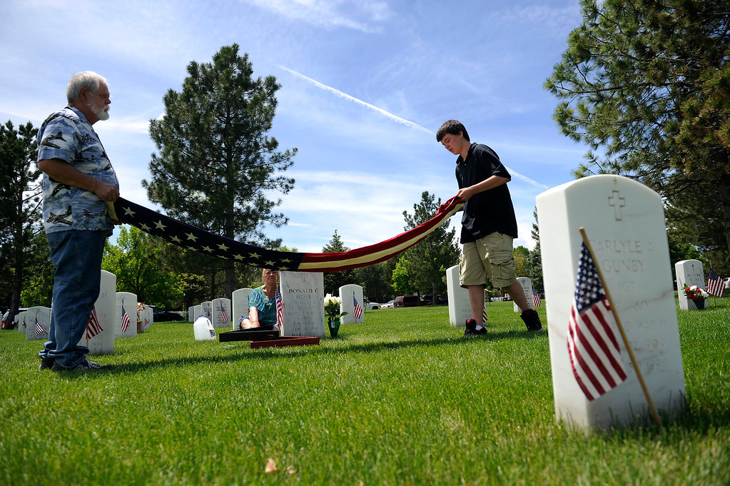 . Donald C Hesse II teaches his grandson Christian Stevens, 16, how to properly fold the American flag in front of the grave of Donald\'s father, Donald C Hesse, during a Memorial Day ceremony at Fort Logan Cemetery in Denver, Colorado on May 26, 2014. (Photo by Seth McConnell/The Denver Post)