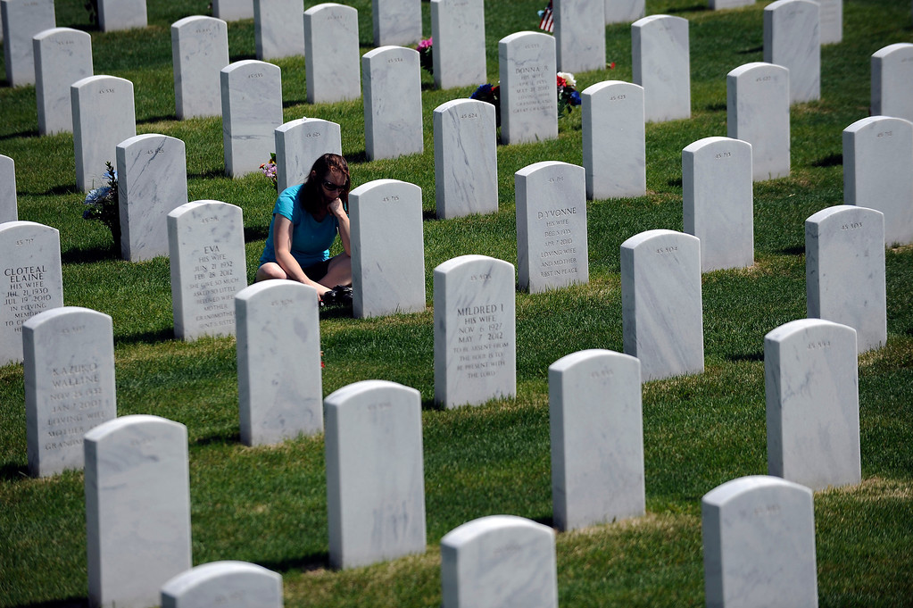 . Marci Cox solemn reflects as she sits in front of her dad, Robert Cox\'s, grave during a Memorial Day ceremony at Fort Logan Cemetery in Denver, Colorado on May 26, 2014. (Photo by Seth McConnell/The Denver Post)