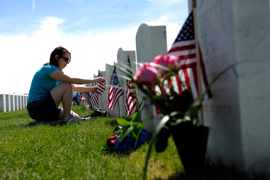 . Marci Cox straightens an American Flag that was placed in front of her dad, Robert Cox\'s, grave during a Memorial Day ceremony at Fort Logan Cemetery in Denver, Colorado on May 26, 2014. (Photo by Seth McConnell/The Denver Post)