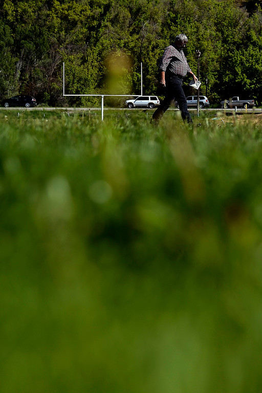 . A man walks across the football field as he and other attendees arrive before the memorial service for the three men who went missing in the Mesa County mudslide. Hundreds of community members gathered for the memorial service at Plateau Valley High School on Sunday, June 01, 2014. (Photo by AAron Ontiveroz/The Denver Post)