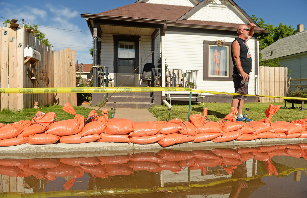 . With little to do but watch and wait Tim Wynne tries to lighten the mood by putting a fishing pole out in front of his home surrounded by flood water in Greeley, June 3, 2014. A flood warning for the Poudre River near Greeley has been extended through Sunday. (Photo by RJ Sangosti/The Denver Post)