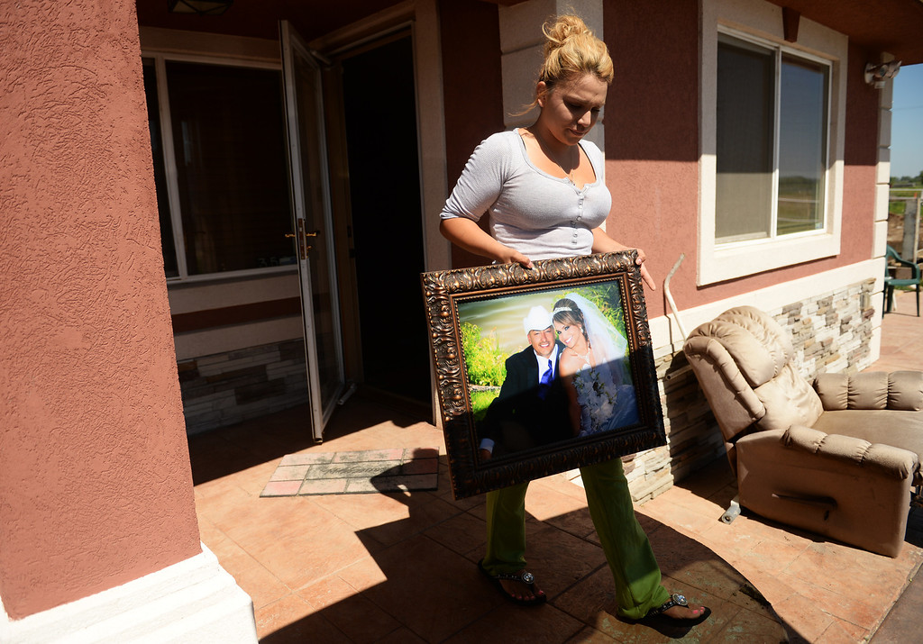 . Erica Nevarez packs a wedding photo into her car at her family\'s home in north Greeley as flood water grows close to the home, June 2, 2014. A flood warning for the Poudre River near Greeley has been extended through Sunday. (Photo by RJ Sangosti/The Denver Post)