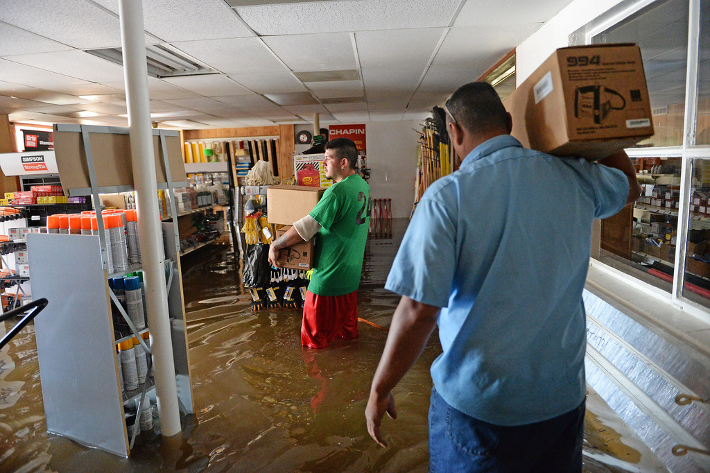 . Jay Torres, left, and Robert Frank Villa, both of DBE Manufacturing and Supply in Greeley, look for items to save from the shop where they work as water continues to rise along the Poudre River, June 3, 2014. A flood warning for the Poudre River near Greeley has been extended through Sunday. (Photo by RJ Sangosti/The Denver Post)