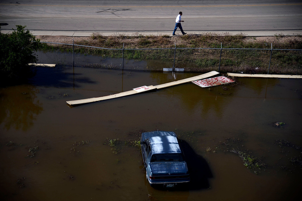 . A man walks near a flooded car as seen from a scissor lift at Thompson\'s Garage Door Service after an area of town flooded near Fourth Avenue. A heavy rain caused parts of Greeley to flood on Monday, June 2, 2014. (Photo by AAron Ontiveroz/The Denver Post)