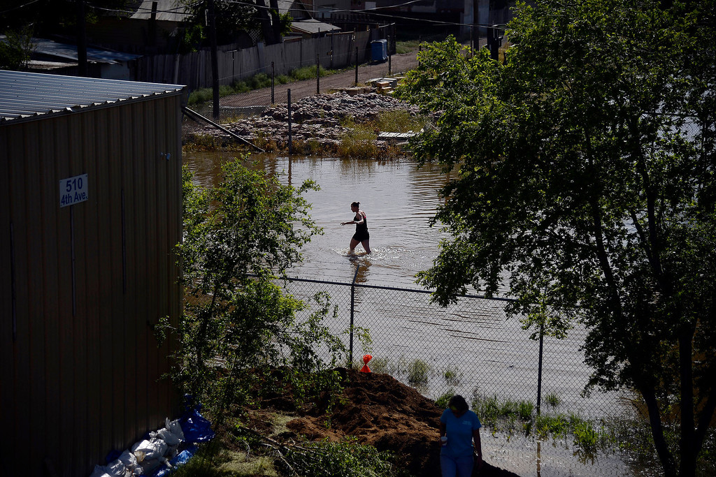 . Jessica Thompson, 16, wades through the water after an area of town flooded near Fifth Avenue and Fifth Street. A heavy rain caused parts of Greeley to flood on Monday, June 2, 2014. (Photo by AAron Ontiveroz/The Denver Post)
