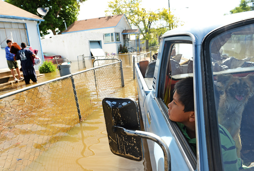 . Ten-year-old Juan Pablo waits in the truck as his family saves items from their flooded home in Greeley as water continues to rise along the Poudre River, June 3, 2014. A flood warning for the Poudre River near Greeley has been extended through Sunday. (Photo by RJ Sangosti/The Denver Post)