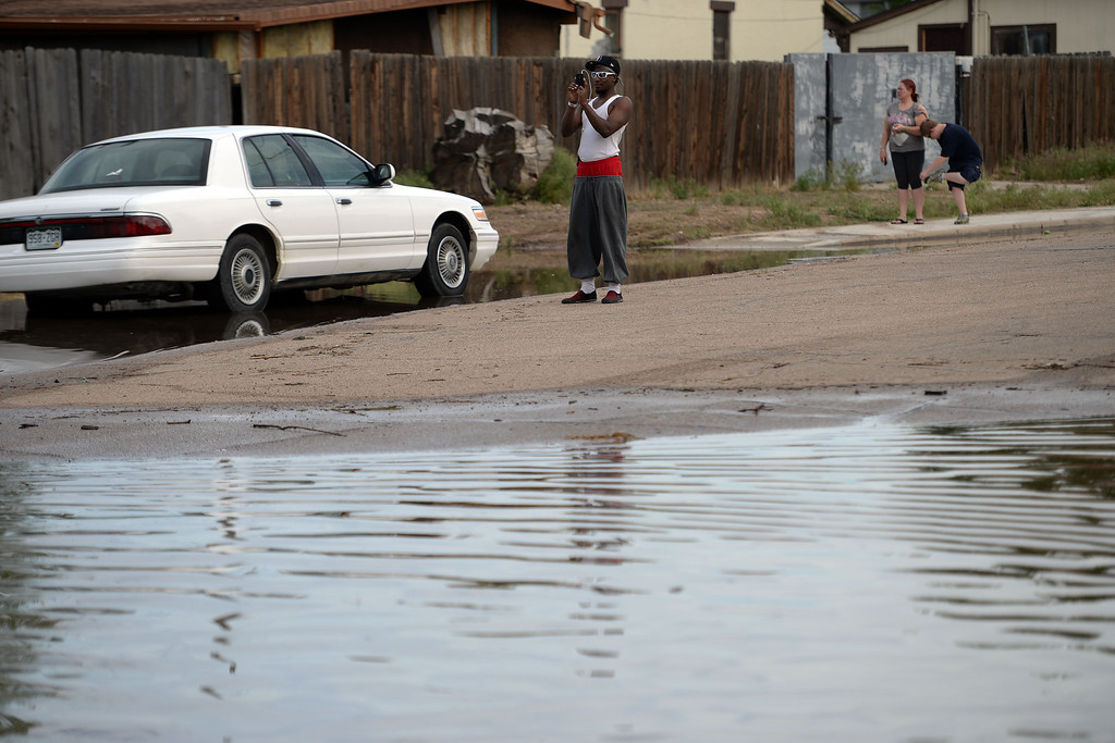 . King Green snaps a picture of the flood waters after an area of town flooded. A heavy rain caused parts of Greeley to flood on Monday, June 2, 2014. (Photo by AAron Ontiveroz/The Denver Post)