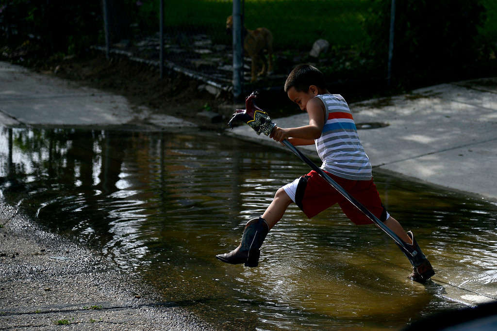 . Gonzalo Conde, 5, jumps over some waster after an area of town flooded near Fourth Street. A heavy rain caused parts of Greeley to flood on Monday, June 2, 2014. (Photo by AAron Ontiveroz/The Denver Post)