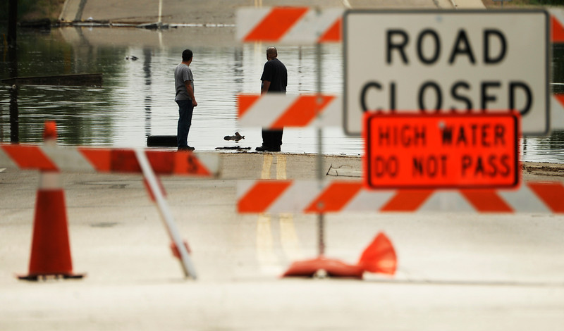 . Two men stand at the waters edge along 5th Street in Greeley as water from the Poudre River floods the area, June 4, 2014. A flood warning for the Poudre River near Greeley has been extended through Sunday. (Photo by RJ Sangosti/The Denver Post)