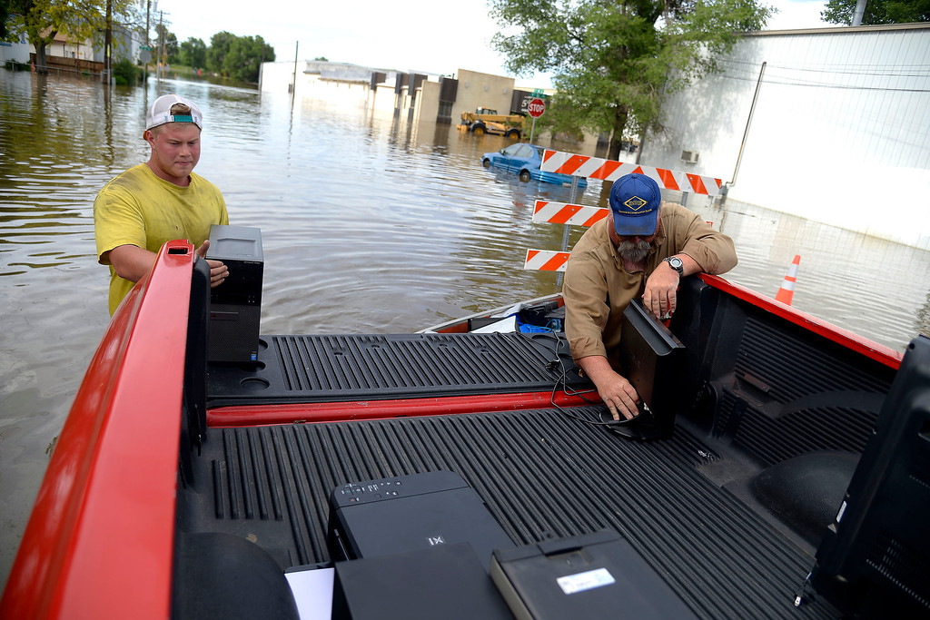 . Keegan Meyer (left) and Jim Trimble save computer equipment from DBE Manufacturing after an area of town flooded.   (Photo by AAron Ontiveroz/The Denver Post)