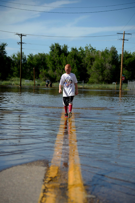 . Evan Thompson wades through the water after an area of town flooded.   (Photo by AAron Ontiveroz/The Denver Post)