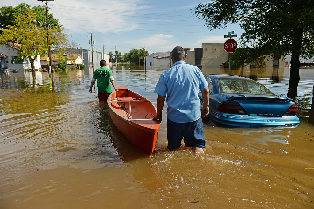 . Jay Torres, left, and Robert Frank Villa, both of DBE Manufacturing and Supply in Greeley, use a boat to save item from the shop where they work as water continues to rise along the Poudre River, June 3, 2014. A flood warning for the Poudre River near Greeley has been extended through Sunday. (Photo by RJ Sangosti/The Denver Post)