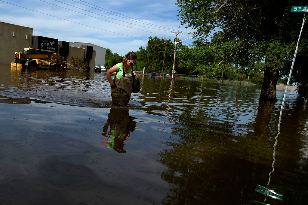 . Natalie Danhoff walks away from DBE Manufacturing after an area of town flooded. A heavy rain caused parts of Greeley to flood on Monday, June 2, 2014. (Photo by AAron Ontiveroz/The Denver Post)