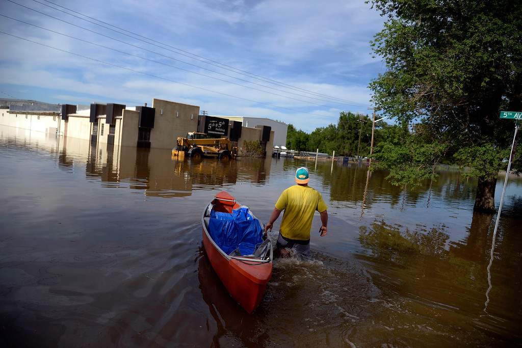 . Keegan Meyer saves equipment from DBE Manufacturing via boat after an area of town flooded. A heavy rain caused parts of Greeley to flood on Monday, June 2, 2014. (Photo by AAron Ontiveroz/The Denver Post)