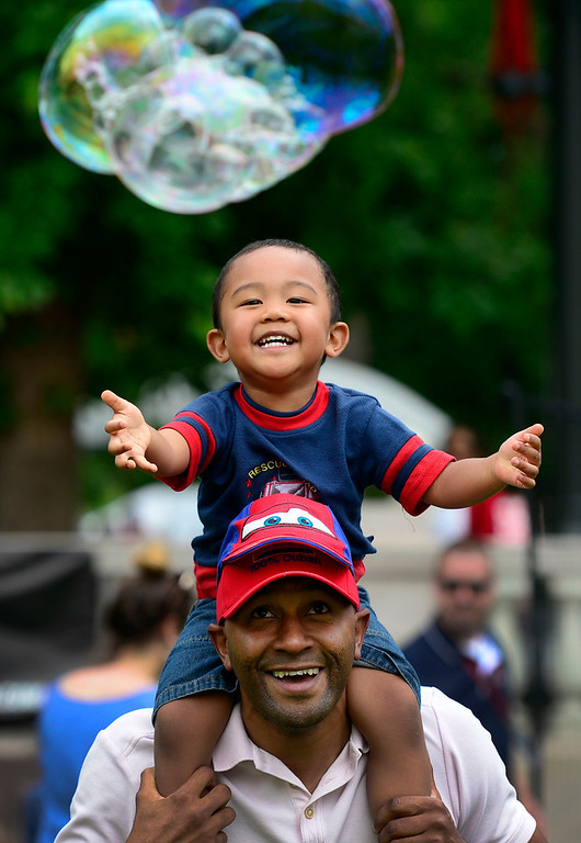 ". DENVER, CO - JUNE 8: Eddy Coello and son Jaylen, 2, from Thornton chase after giant bubbles from the Eco-friendly bubble tower. The Annual CHUN Capitol Hill People\'s Fair takes place at Civic Center Park in downtown Denver. The fair emphasizes ""bringing together a diverse population to celebrate community and enjoy the start of the summer festival season\"". The fair includes live entertainment with vendors selling food, arts and crafts, kids activities as well as numerous non-profits representing various organizations. The event runs through Sunday, 10 am to 7 pm. (Photo by Kathryn Scott Osler/The Denver Post)"