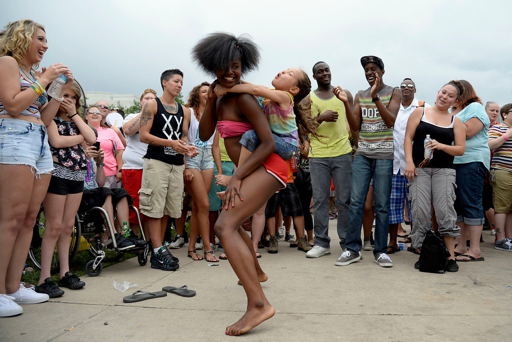 . DENVER, CO - JUNE 22: Lillian Smith dances with Armani Montez, 5, on her back during PrideFest 2014 in downtown Denver. Thousands of people gathered in the city to enjoy a bevy of events including dancing, food and music on Sunday, June 22, 2014. (Photo by AAron Ontiveroz/The Denver Post)