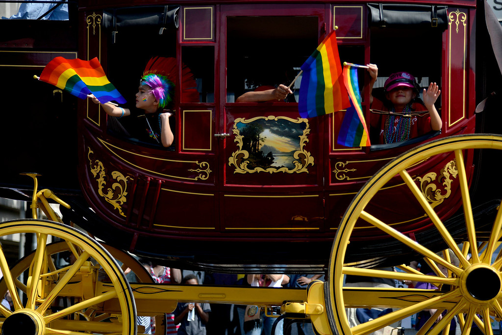 . DENVER, CO - JUNE 22: Children wave pride flags from within the Wells Fargo stagecoach during the PrideFest 2014 parade in downtown Denver. Thousands of people gathered in the city to enjoy a bevy of events including dancing, food and music on Sunday, June 22, 2014. (Photo by AAron Ontiveroz/The Denver Post)