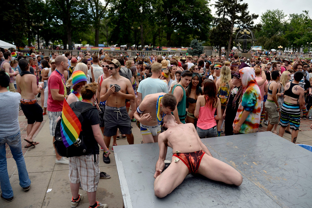 . DENVER, CO - JUNE 22: Brian Ogden (standing) kisses dancer Dylan Seyers during PrideFest 2014 in downtown Denver. Thousands of people gathered in the city to enjoy a bevy of events including dancing, food and music on Sunday, June 22, 2014. (Photo by AAron Ontiveroz/The Denver Post)