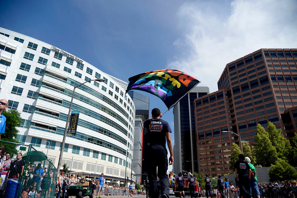 ". DENVER, CO - JUNE 22: Kathleen Hancock of the Aurora Fire Department waves a flag reading, ""Born This Way,\"" during PrideFest 2014 in downtown Denver. Thousands of people gathered in the city to enjoy a bevy of events including dancing, food and music on Sunday, June 22, 2014. (Photo by AAron Ontiveroz/The Denver Post)"