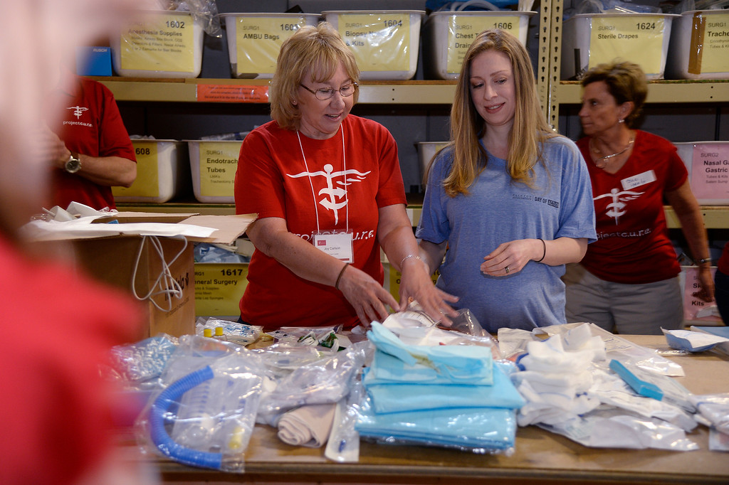 . Joy Calrson (L) puts together medical supplies with Chelsea Clinton at Project C.U.R.E. in Centennial.  (Photo by John Leyba/The Denver Post)