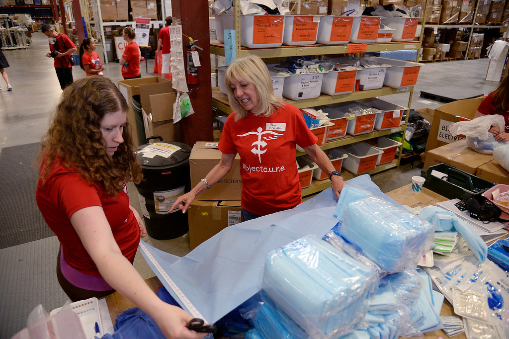 . Martha Taylor (L) and Pam Chandler with Project C.U.R.E. put together Medical Supplies and Equipment in boxes to be shipped out. (Photo by John Leyba/The Denver Post)