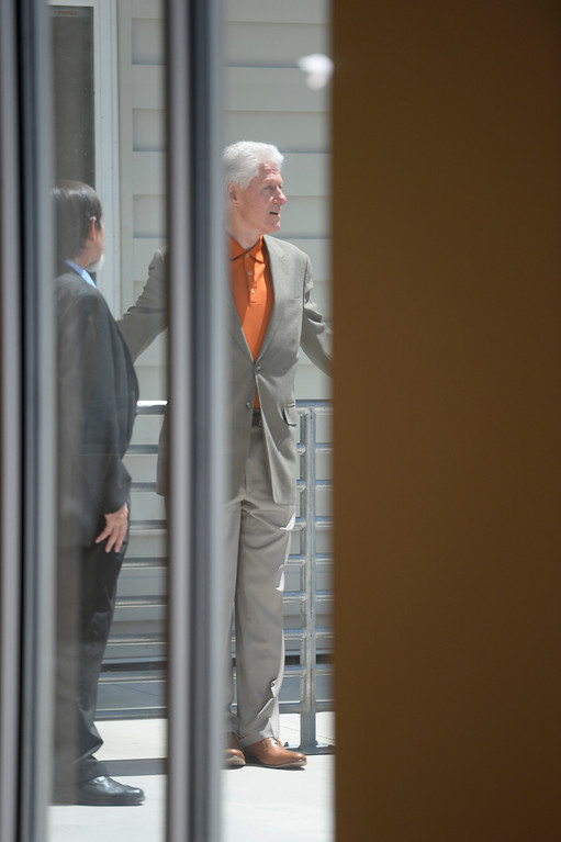 . President Bill Clinton steps out on the balcony from the community room where John Parvensky, President of the Colorado Coalition for the Homeless gives him a tour of the new Stout Street Health Center and Renaissance Stout Street Lofts June 23, 2014, the latest development from the Colorado Coalition for the Homeless to address homelessness in Metro Denver.  The tour was in conjunction with the Clinton Global Initiative (CGI) America meeting in Denver. (Photo by John Leyba/The Denver Post)