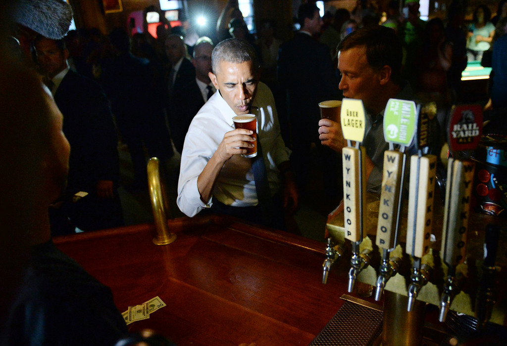 . DENVER, CO - JULY 08: President Barack Obama orders a beer with Colorado Governor John Hickenlooper at Wynkoop Brewery in downtown Denver after arriving in Colorado, July 08, 2014. President Obama is in Colorado to speak about the economy and raise money for Senator Mark Udall\'s re-election campaign. (Photo by RJ Sangosti/The Denver Post)