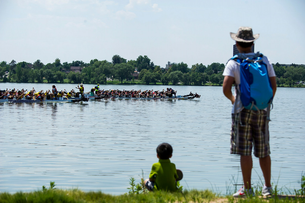 . Skylar Seukpanya and his father Sisouk Seukpanya watch a Hong Kong style Dragon Boat Race during the 2014 Colorado Dragon Boat Festival at Sloan\'s Lake Park on Sunday, July 20, 2014 in Denver, CO.  The event featured 100 performances on 5 stages, 21 food vendors in two food Taste of Asia courts, more than 40 Marketplace Exhibitors, and the exciting ancient sport of Dragon Boat Racing.  (Photo by Kent Nishimura/The Denver Post)