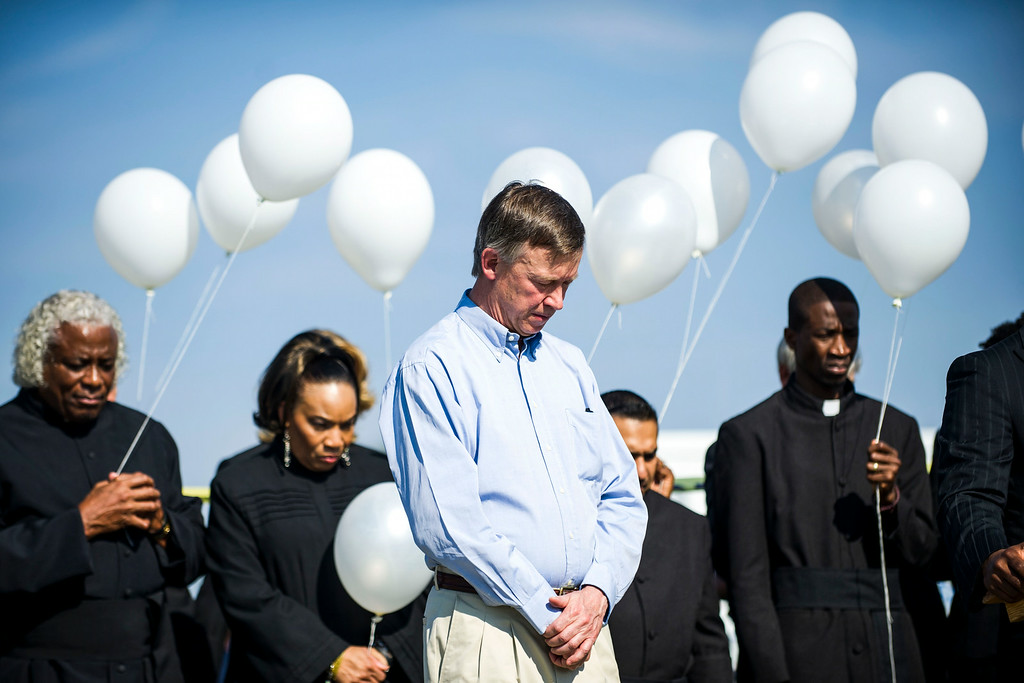 . Colorado Governor John Hickenlooper bows his head during a prayer at a dedication ceremony for the newly planted trees at Hope Park at The Potter\'s House of Denver on Sunday, July 20, 2014 in Aurora, CO.  Each tree planted bore a yellow ribbon with the name of a person who lost their life in the tragedy.  (Photo by Kent Nishimura/The Denver Post)