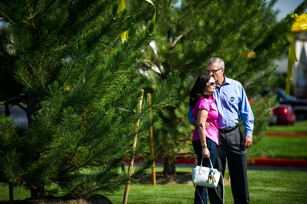 . Tom Teves kisses his wife, Caren Teves while they pose for a picture in front of  a tree adorned with a ribbon bearing the name of their son, Alex Teves, who was killed in the during a dedication ceremony for the newly planted trees at Hope Park at The Potter\'s House of Denver on Sunday, July 20, 2014 in Aurora, CO.  Each of the thirteen trees planted bore a yellow ribbon with the name of a person who lost their life in the tragedy.  (Photo by Kent Nishimura/The Denver Post)