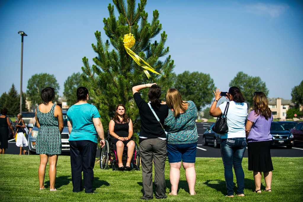 . Ashley Moser poses for a picture in front of a tree bearing a ribbon for her 6 year old daughter Veronica Moser-Sullivan, who was killed in the attack on the Century Aurora 16 movie theater, after the conclusion of a dedication ceremony for the newly planted trees at Hope Park at The Potter\'s House of Denver on Sunday, July 20, 2014 in Aurora, CO.  Each tree planted bore a yellow ribbon with the name of a person who lost their life in the tragedy.  (Photo by Kent Nishimura/The Denver Post)