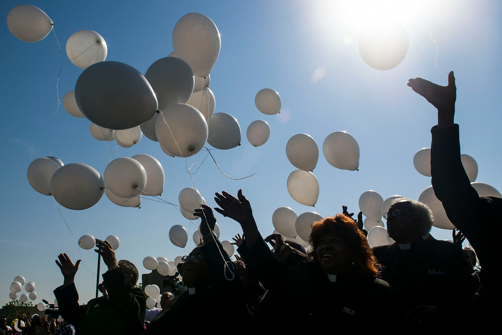 . People release balloons into the air during a dedication ceremony for the newly planted trees at Hope Park at The Potter\'s House of Denver on Sunday, July 20, 2014 in Aurora, CO.  Each tree planted bore a yellow ribbon with the name of a person who lost their life in the tragedy.  (Photo by Kent Nishimura/The Denver Post)
