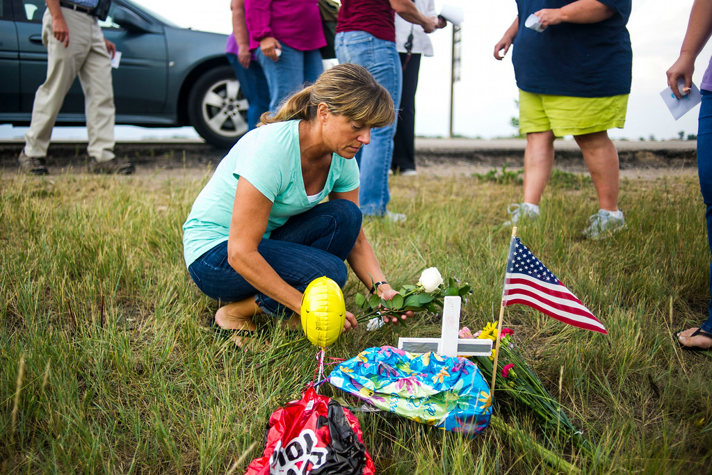 . Dorothy Gibson places flowers at a small roadside memorial at an eagle\'s nest along E120th Avenue near, E-470 on Sunday, July 27, 2014 in Commerce City, Colorado. (Photo by Kent Nishimura/The Denver Post)