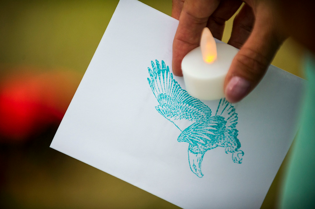. Dorothy Gibson holds a battery-powered candle and a card with a bald eagle stamp at an eagle\'s nest along E120th Avenue near, E-470 on Sunday, July 27, 2014 in Commerce City, Colorado.  The eaglet (Photo by Kent Nishimura/The Denver Post)