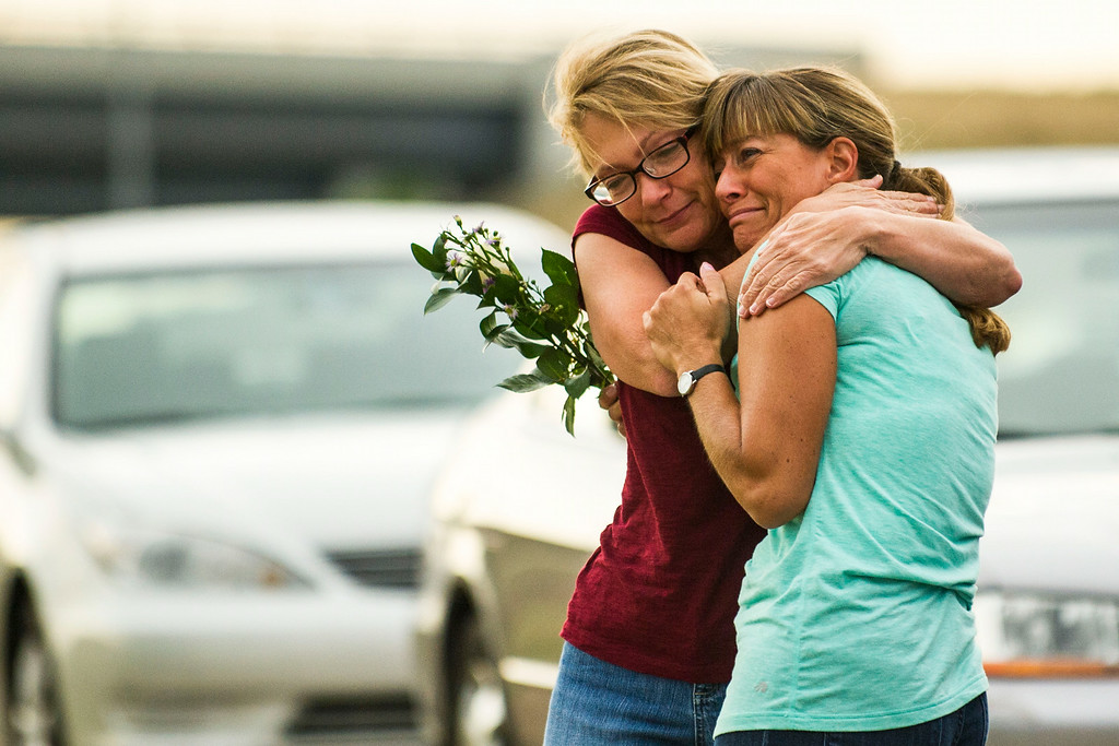 . Volunteers Karen Blackwood and Dorothy Gibson hug after arriving a small gathering to honor the eaglet that the Raptor Education Foundation had been observing at an eagle\'s nest along E120th Avenue near, E-470 on Sunday, July 27, 2014 in Commerce City, Colorado.  (Photo by Kent Nishimura/The Denver Post)