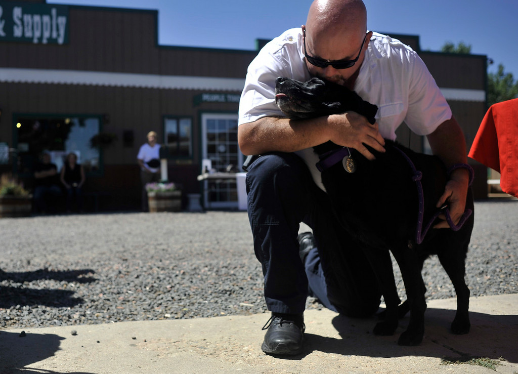 ". BROOMFIELD, CO. - AUGUST 2: Colorado Bureau of Investigation Arson Investigator Agent Jerry Means kisses his retiring partner Sadie, an accelerant detection canine, during her retirement ceremony at Willow Run Feed & Supply in Broomfield Saturday, August 2, 2014. ""We\'re buddies,\"" says Means. \""We\'ve spent almost every day together since 2007.\"" After Sadie\'s retirement, Means\' new dog Riley was sworn in. (Photo By Patrick Traylor/The Denver Post)"