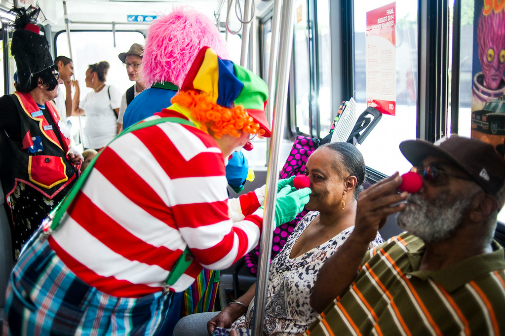 . DENVER, CO - AUGUST 04:  Lynn Imig, Sprinkles the Clown, gives clown noses to Earliee Walker and Oscar Henderson while riding the Mall Ride along the 16th Street Mall on Monday, August 04, 2014 in Denver, Colorado.  The members of the Colorado Clown Alley were out at Union Station and the 16th Street Mall in celebration of International Clown Week which runs from August 1-7.  (Photo by Kent Nishimura/The Denver Post)