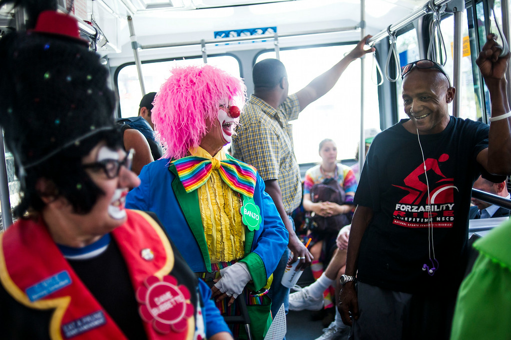 . DENVER, CO - AUGUST 04:  Lorene Stadig, Banjo the Clown, shares a light moment with passenger Rodney Daniel on the Mall Ride at the 16th Street Mall on Monday, August 04, 2014 in Denver, Colorado.   The members of the Colorado Clown Alley were out at Union Station and the 16th Street Mall in celebration of International Clown Week which runs from August 1-7.  (Photo by Kent Nishimura/The Denver Post)
