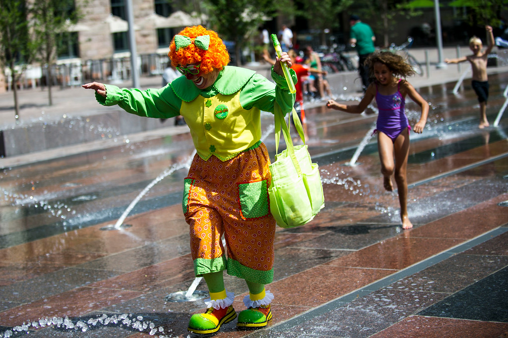 . DENVER, CO - AUGUST 04:  Kathy Shook, Sami-Ann the Clown, runs thorough the Union Station South Plaza fountain on Monday, August 04, 2014 in Denver, Colorado.   The members of the Colorado Clown Alley were out at Union Station and the 16th Street Mall in celebration of International Clown Week which runs from August 1-7.  (Photo by Kent Nishimura/The Denver Post)
