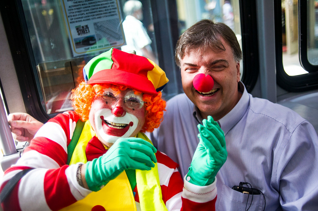. DENVER, CO - AUGUST 04:  Lynn Imig, Sprinkles the Clown,  shares a light moment with passenger Robert Foster after giving him a clown nose while riding the mall ride along the 16th Street Mall on Monday, August 04, 2014 in Denver, Colorado.  The members of the Colorado Clown Alley were out at Union Station and the 16th Street Mall in celebration of International Clown Week which runs from August 1-7.  (Photo by Kent Nishimura/The Denver Post)