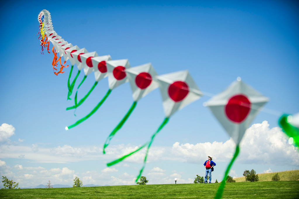 . DENVER, Colorado - AUGUST 06:  Kite Artist Scott Skinner looks on as Japanese Kite Master Mikio Toki flies a kite train or Rendako, made up of 150 individually connected kites, during the Japanese Kite Festival at the Pavilion at Stapleton Central Park on Wednesday, August 06, 2014 in Denver, Colorado.  The event featured a demonstration by Japanese Kite Master Mikio Toki of Japan and a chance to make your own kites.  (Photo by Kent Nishimura/The Denver Post)