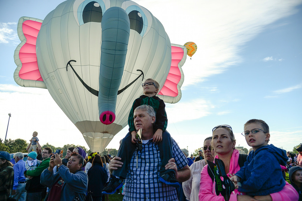 . Don Barett hold grandson Jadon, 6, on his shoulders as Chelsie Barrett holds Jaxon Barrett, 4, as hundreds of balloon enthusiasts gather to watch the launch of The 2014 Colorado Balloon Classic. (Photo by John Leyba/The Denver Post)